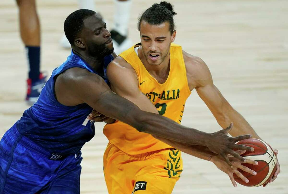 Xavier Cooks (right) drives against U.S. defender Draymond Green during Australia's 91-83 exhibition victory in Las Vegas.