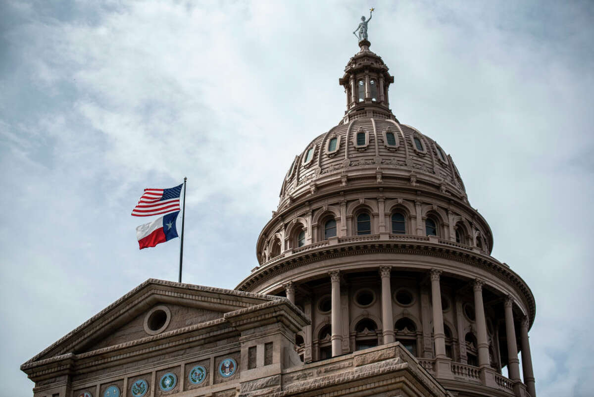 AUSTIN, TX - JULY 12: The U.S. and Texas state flags fly over the state Capitol building on July 12, 2021 in Austin, Texas. Texas Democrats have fled the state in order to prevent a quorum in protest over a Republican voting protection bill that they say is too restrictive.