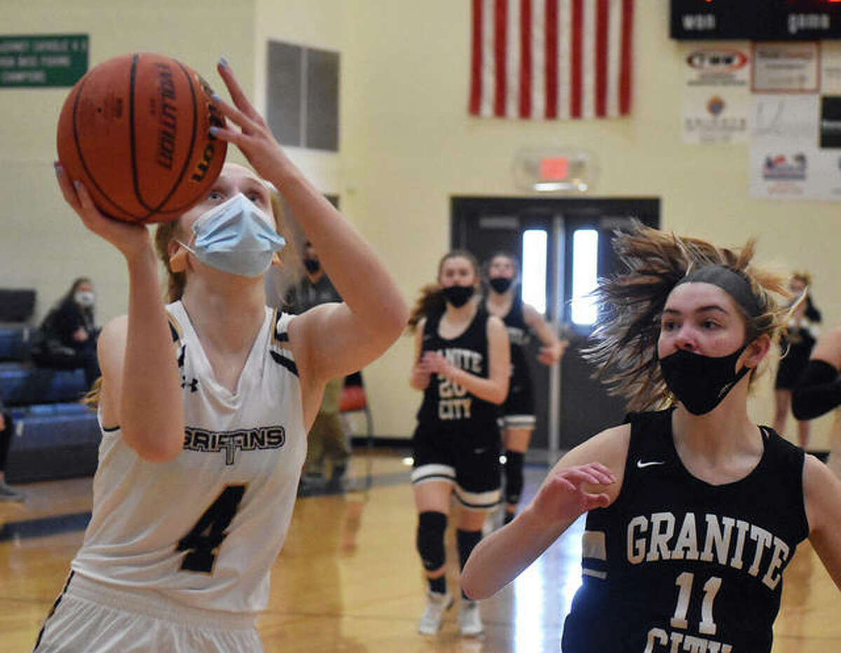 Father McGivney senior guard Anna McKee, left, goes up for a lay-in after stealing the ball at midcourt during the home opener against Granite City.