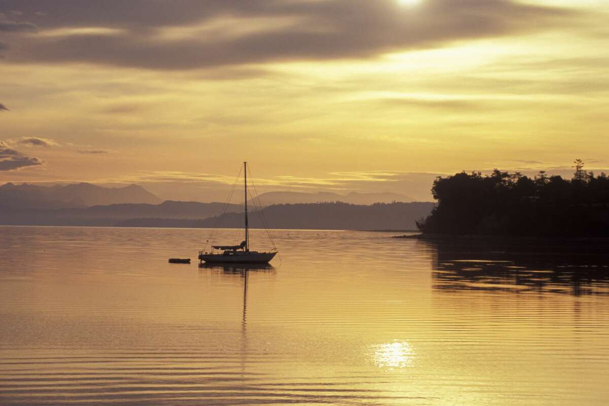 A yacht is silhouetted at sunrise over Penn Cove off the waterfront seaport town of Coupeville on Whidbey Island.