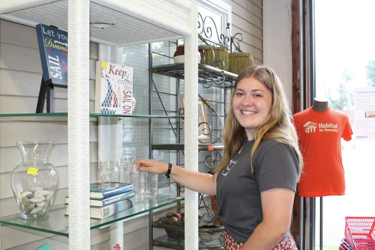 Housatonic Habitat for Humanity intern Olivia Seal, 19, adjusts a display near the front entrance of the organization's ReStore facility on Austin Street in Danbury.