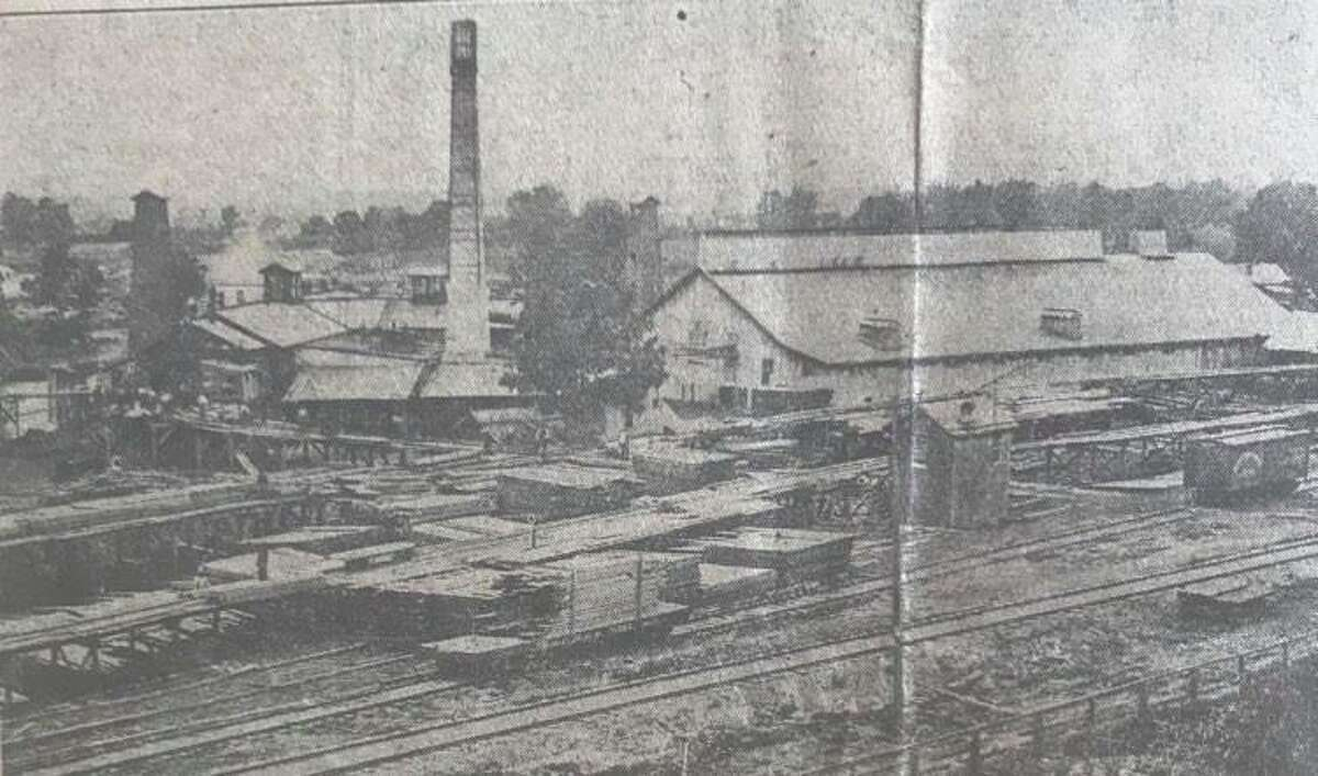 """The Patrick Saw Mill and Salt Block at the foot of McDonald Street in the late 1880s. The mill was founded by John Larkin in 1855. The two brine wells were those from which H.H. Dow took samples of brine in 1890, before he settled in Midland. In 1892, a boiler explosion wrecked most of the mill, purchased from Larkin by the Midland Salt and Lumber Co. The tall chimney shown in the photo was razed by the blast and killed a workman in its fall. A flying piece of steel from the boilers near the chimney killed an """"edgerman"""" in the mill. A May 12, 1892, headline in the Midland Republican, the forerunner of the Midland Daily News, stated, """"The most horrible disaster that has ever visited Midland."""""""