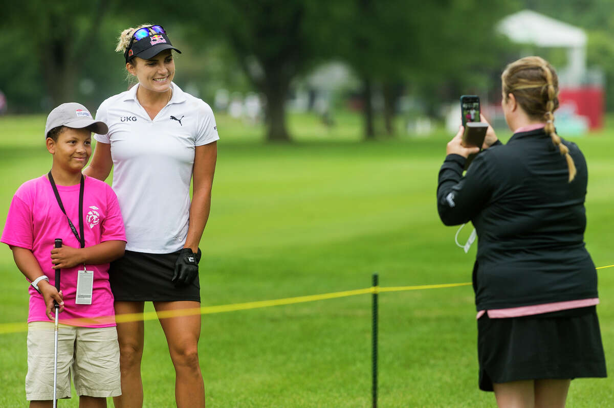 Katie Lewis of Midland, right, snaps a photo of her son Jaxson, 10, left, with LPGA player Lexi Thompson, center, as Jaxson volunteers during the Dow Great Lakes Bay Invitational Pro Am tournament Tuesday, July 13, 2021 at the Midland Country Club. (Katy Kildee/kkildee@mdn.net)