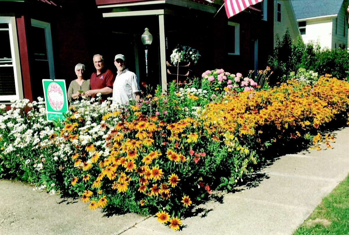 TheSpirit of the Woods Garden ClubInc. recently presented the June 2021 Garden of the Month award. Pictured (left to right) are garden club member Mary Metzger and winners Dennis Dalton and Jayme Payne. (Courtesy photo)