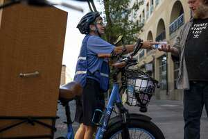 Sister Libby Fernandez, executive director with Mercy Pedalers, left, hands a bottle of water to a person experiencing homelessness during a heatwave in Sacramento, Calif., on July 8, 2021.