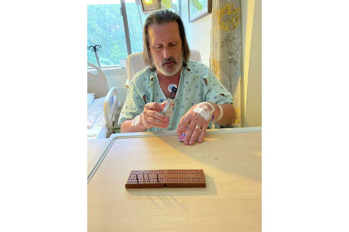 The columnist's husband, Brian, plays a game of cribbage after a series of surgeries.