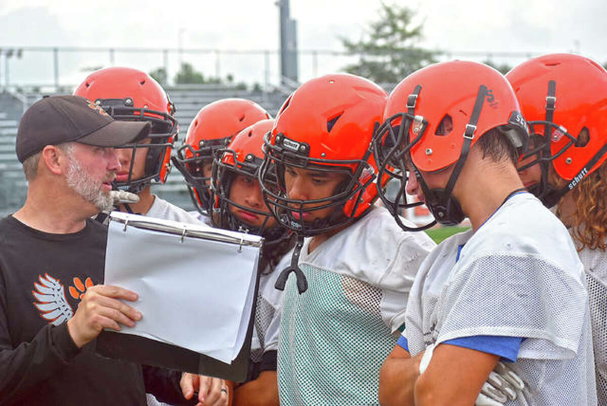 Edwardsville assistant coach Carry Bailey talks to a group of receivers before a 7-on-7 drill at Tuesday's practice.