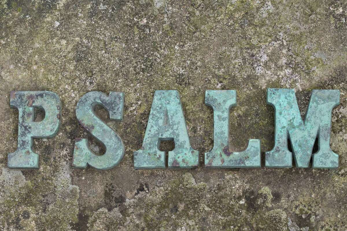 """Close up of iron cast letters forming the word """"psalm"""" on top of a stone surface."""
