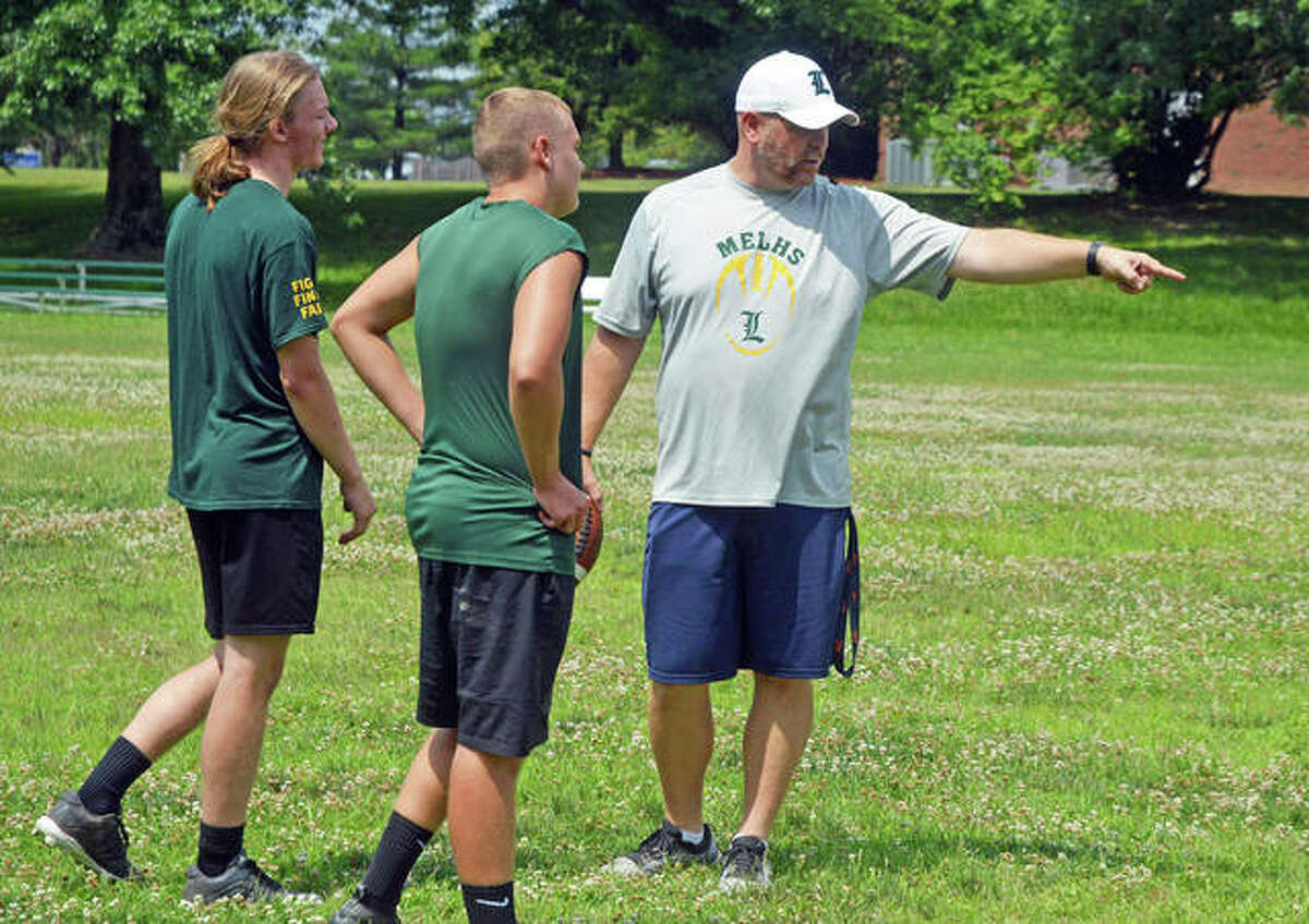 Metro-East Lutheran football coach Mike Koch, right, talks to seniors Kaiden Downs, left, and Peyton Wren during a summer practice session last week.