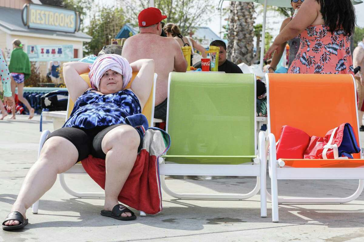 Ashley Giovacchini lounges near the pool at South Bay Shores water park at California's Great America in Santa Clara, Calif. The Bay Area's first summer heat wave is expected to descend on the region in the coming days.
