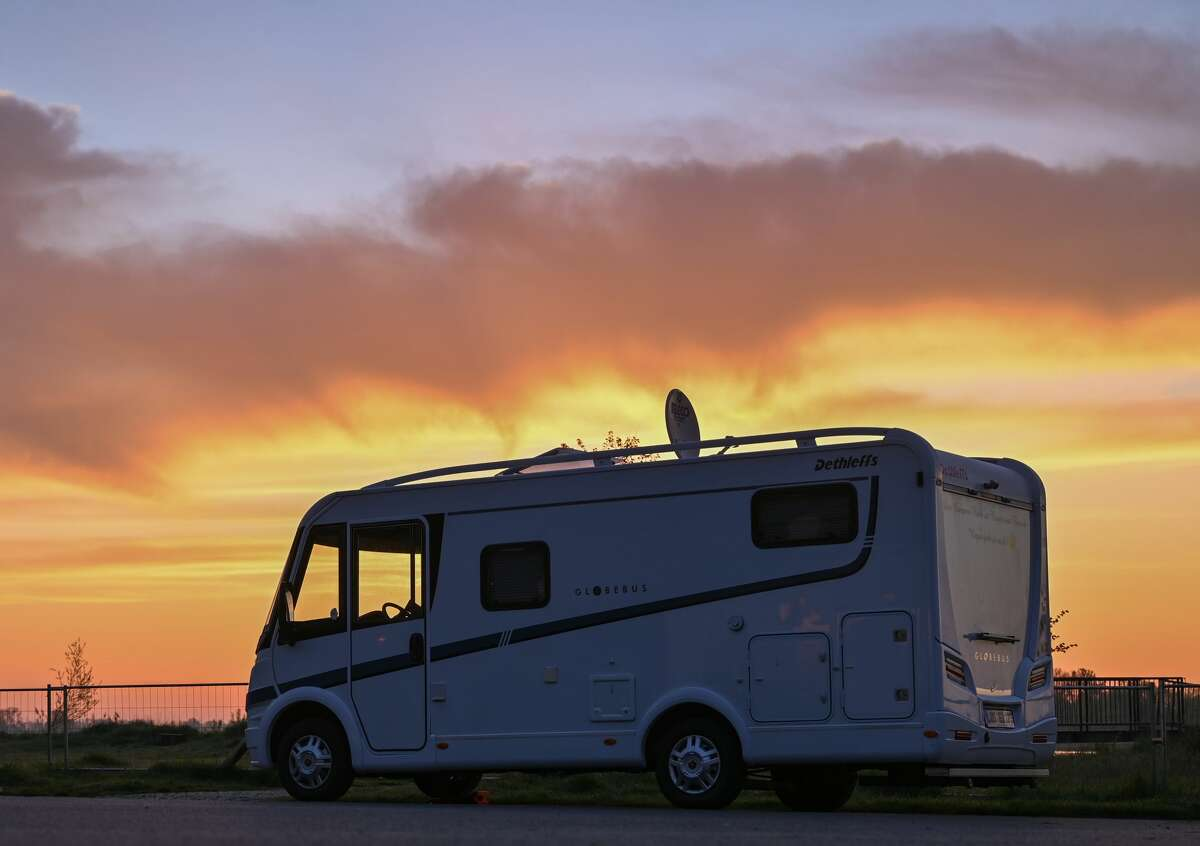 In the early morning sunrise a motorhome stands on a parking lot at the German-Polish border river Oder at the edge of the Oderbruch in East Brandenburg.