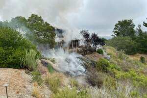 A home on fire after a plane crashed near Monterey Regional Airport on July 13, 2021.