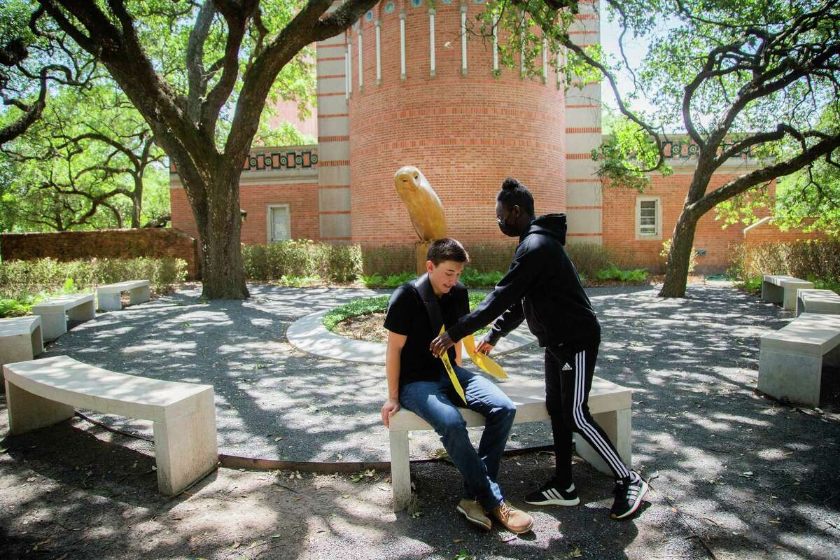 Rice University student L. Diop, right, helps also student Jason Gardner, left, get ready for a graduation photoshoot in campus, Monday, April 26, 2021, in Houston. Rice University ranked highest in Texas in SmartAssets' rankings, with a score of 73.07 on a 100-point scale. The Houston-based, private university has the highest tuition, but also offered the largest average scholarships and grants, and its students graduated to an average salary of $72,400 a year.