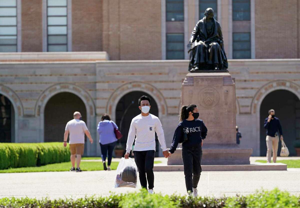 People walk on the campus of Rice University near the statue of the school's namesake, William Marsh Rice, Thursday, April 1, 2021 in Houston.