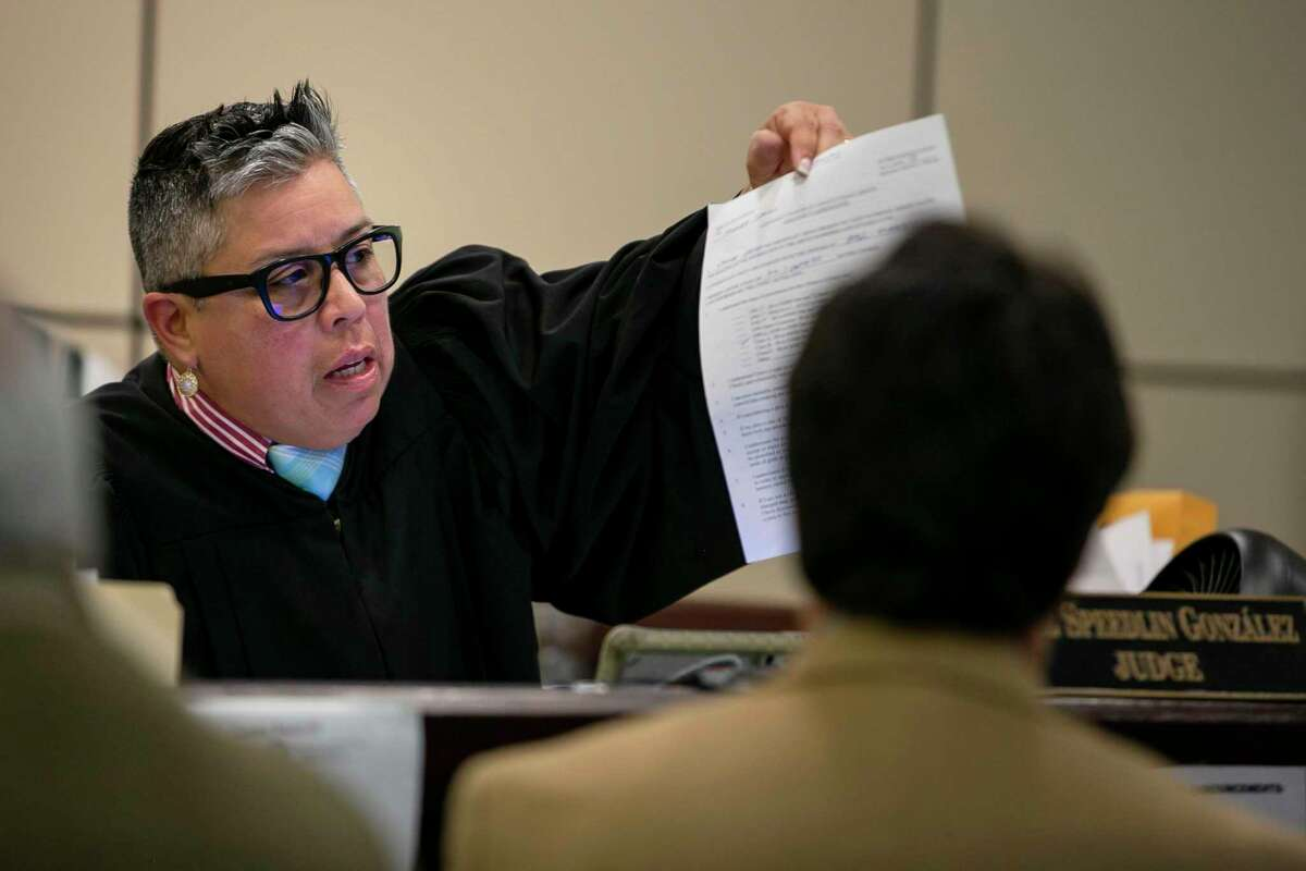 Judge Rosie Speedlin Gonzalez shows a document to a defendant during proceedings in County Court 13, which focuses on family violence cases. A protective order plays a part in ending domestic violence.
