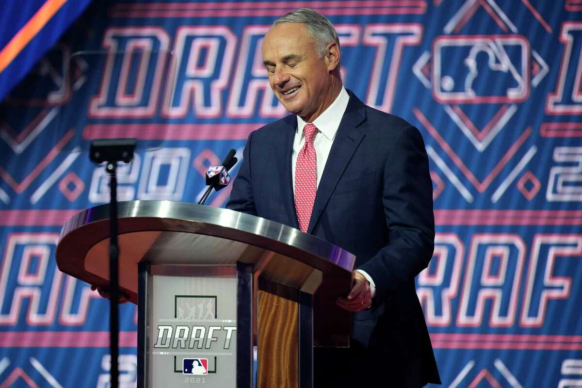 MLB Commissioner Rob Manfred reacts as he is booed by fans during the first round of the 2021 MLB baseball draft, Sunday, July 11, 2021, in Denver. (AP Photo/David Zalubowski)