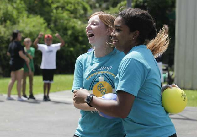 Counselor Makinsey Exley, left, hugs Nia Ford got the final out during a game of dodgeball against members of the Conroe Police Department at the Oscar Johnson, Jr. Community Center, Tuesday, July 13, 2021, in Conroe. Photo: Jason Fochtman/Staff Photographer / 2021 ? Houston Chronicle