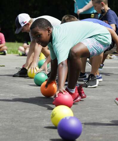 Campers rush to get balls as they play a game of dogeball at the Oscar Johnson, Jr. Community Center, Tuesday, July 13, 2021, in Conroe. Photo: Jason Fochtman/Staff Photographer / 2021 © Houston Chronicle