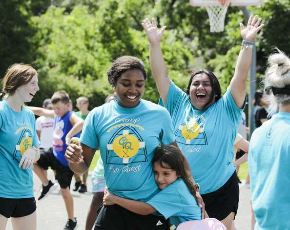 Counselor Nia Ford, center, is hugged by camper Annabella Guidry as fellow counselor Jaylene Acosta cheers after getting the final out during a game of dodgeball against members of the Conroe Police Department at the Oscar Johnson, Jr. Community Center, Tuesday, July 13, 2021, in Conroe. The game gave campers and staff the opportunity to build relationships with members of law enforcement. Photo: Jason Fochtman/Staff Photographer / 2021 ? Houston Chronicle