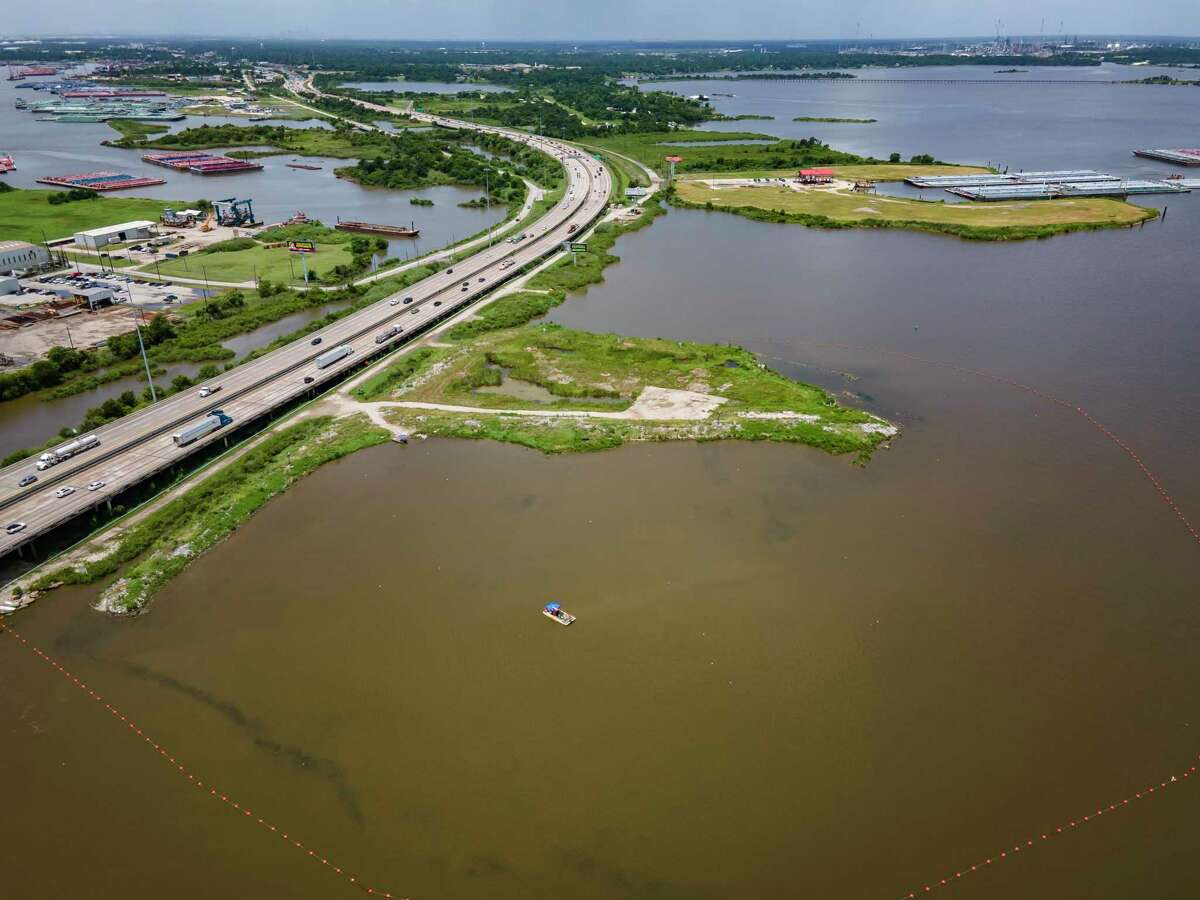 A line of buoys marks the boundary of the northern impoundments of the San Jacinto Waste Pits just north of Interstate 10 on the San Jacinto River, Tuesday, July 13, 2021, in Channelview. The southern impoundments of the superfund site are on the small peninsula south of the freeway.