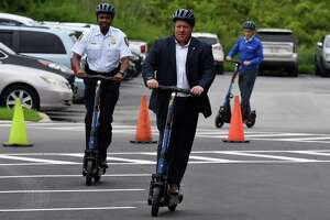 Albany County Executive Dan McCoy, center, Albany Police Chief Eric Hawkins, left, and Capital District Transportation Authority CEO Carm Basile, right, take a ride on the new CDTA electric rental scooters on Tuesday, July 13, 2021, during an event to promote the new vehicles at CDTA headquarters in Albany, N.Y. Scooters will be available at racks throughout the Capital Region and cost 25 cents per minute, plus a $2 fee to unlock, using a mobile app. They will be available from 6 a.m. to 11 p.m. (Will Waldron/Times Union)