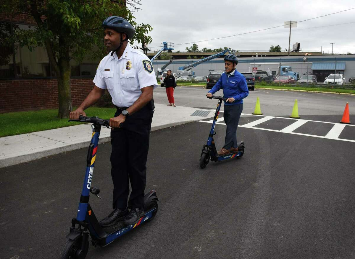 Albany Police Chief Eric Hawkins, left, and Capital District Transportation Authority CEO Carm Basile, right, take a ride on the new CDTA electric rental scooters on Tuesday, July 13, 2021, during an event to promote the new vehicles at CDTA headquarters in Albany, N.Y. Scooters will be available at racks throughout the Capital Region and cost 25 cents per minute, plus a $2 fee to unlock, using a mobile app. They will be available from 6 a.m. to 11 p.m. (Will Waldron/Times Union)