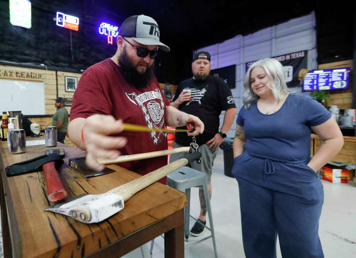 Jorge Sanchez, left, messures an ax as he takes a custom order for Haillie DePaolo during Texas Ax Throwing's summer league competition, Tuesday, July 6, 2021, in Spring.