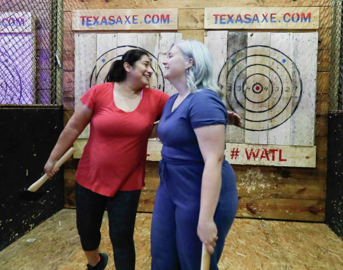 Kim Sauceda, left, hugs Haillie DePaolo after the two competed against eachother during in Texas Ax Throwing's summer league competition, Tuesday, July 6, 2021, in Spring.