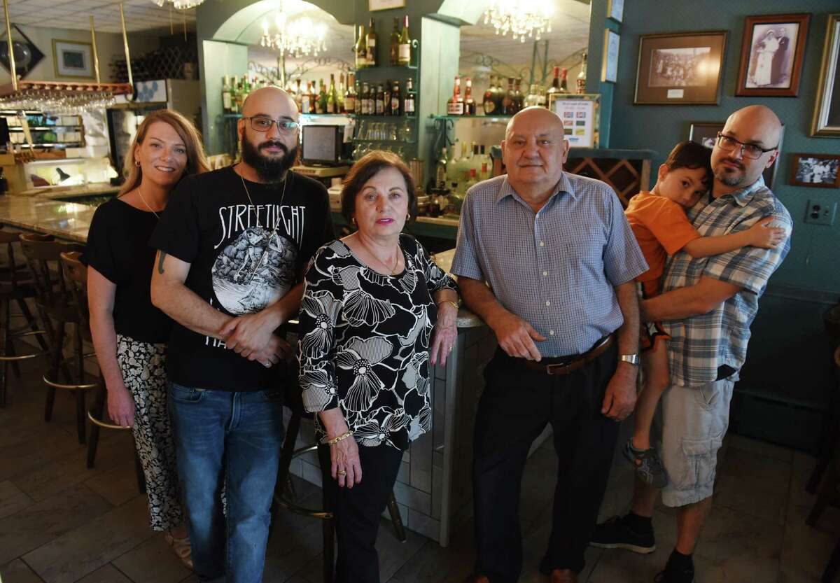 Sam's Italian American Restaurant co-owner's Carmela Rappoccio Daubney, center left, and brother, Paul Rappoccio, are pictured in the restaurant bar with family members; Gina Garrison, left, Joe Rappoccio and Arlo and Paul Rappoccio, right, on Tuesday, July 13, 2021, on Southern Boulevard in Albany, N.Y. The Albany restaurant closed permanently just three months after celebrating its 50th anniversary. (Will Waldron/Times Union) Gina Garrison