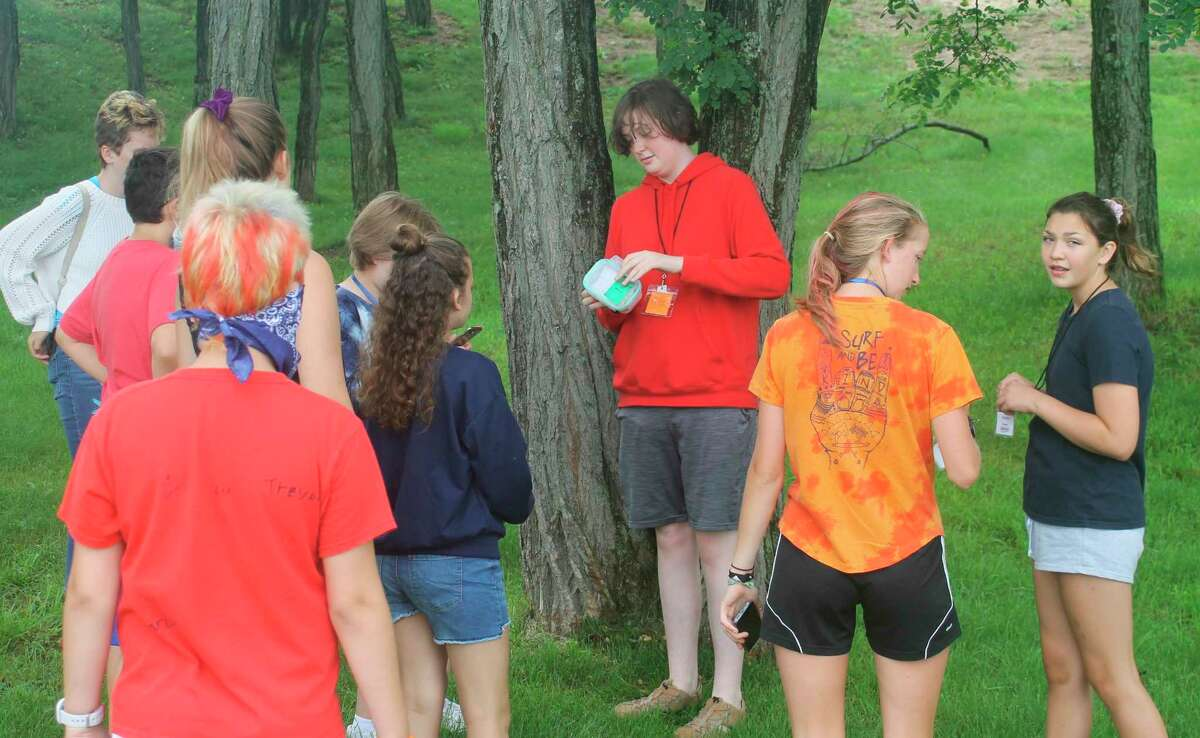 Armory Youth Project students examine a geocache found near the First Street Beach softball fields on Tuesday. Geocachine is a recreational activity in which people search for small containers using GPS coordinates. (Kyle Kotecki/News Advocate)