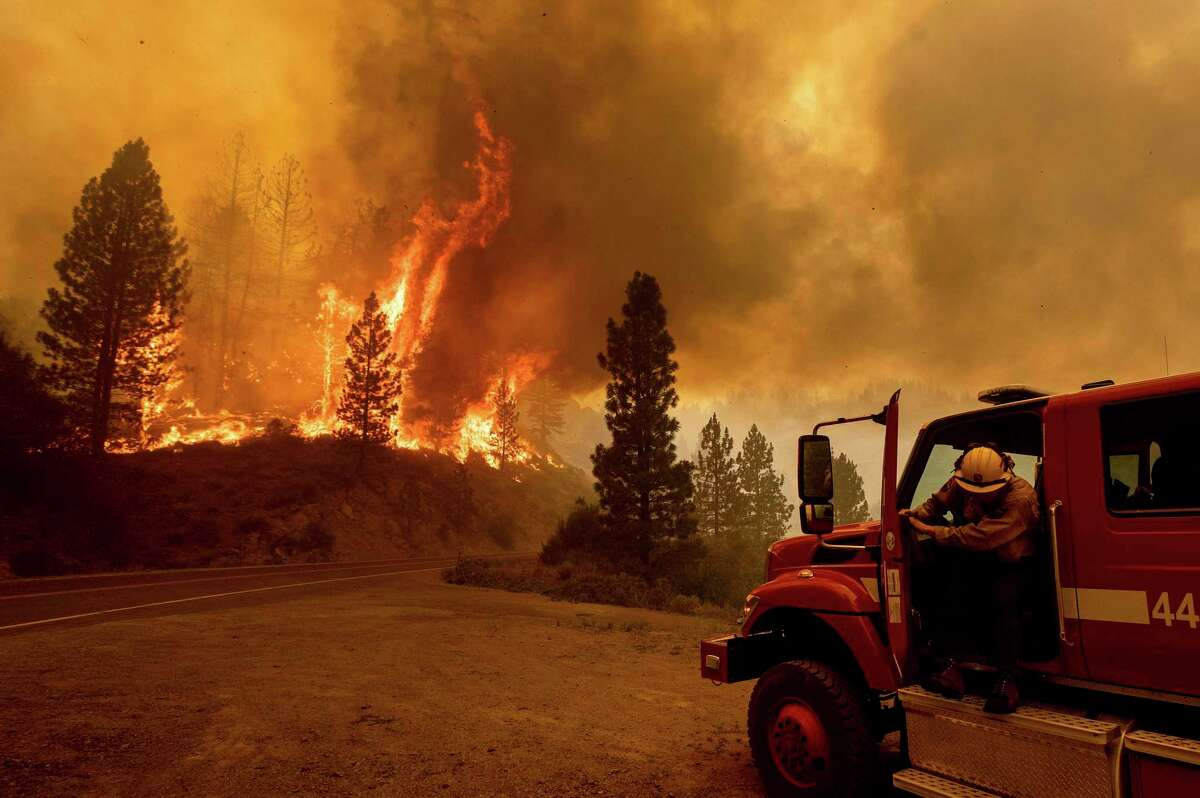 A firefighter prepares to battle the Sugar Fire, part of the Beckwourth Complex Fire, on Thursday in the Plumas National Forest.