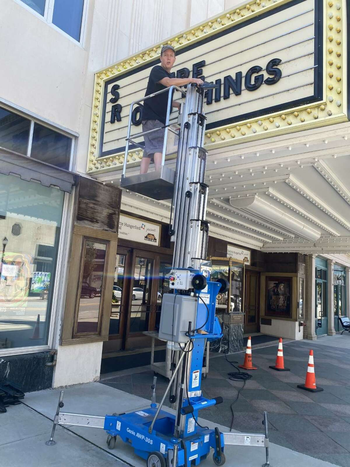 Woody Dick, the Warner Theatre's tech director, sets lettering on the theater's marquee for upcoming events, now that pandemic restrictions have eased.