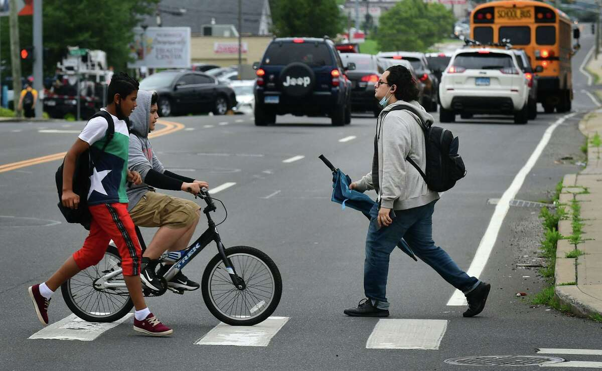 Pedestrians and bicyclists navigate the intersection at Connecticut and Taylor Avenues Tuesday, July 13, 2021, in Norwalk, Conn. A teen was hit by a motor vehicle there while on his bike last month.