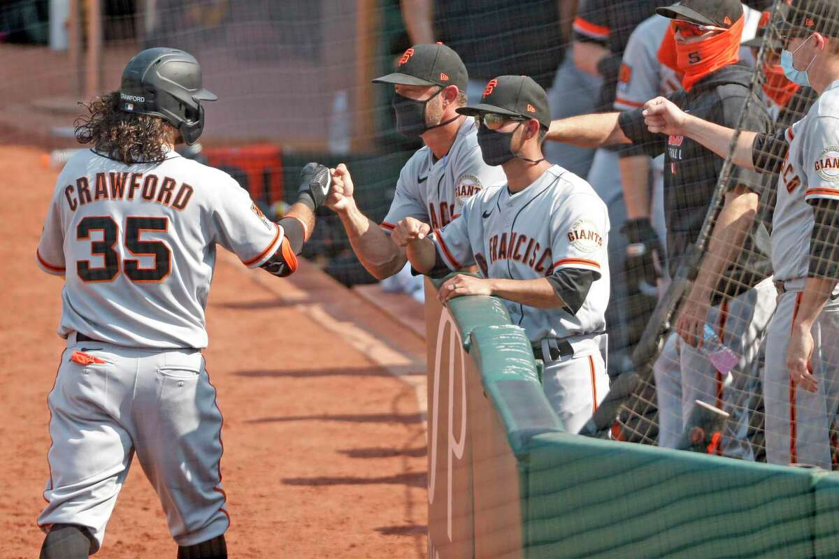 San Francisco Giants' Brandon Crawford is greeted by manager Gabe Kapler after Crawford's 6th inning grand slam against Oakland Athletics in MLB game at Oakland Coliseum in Oakland, Calif., on Sunday, September 20, 2020.