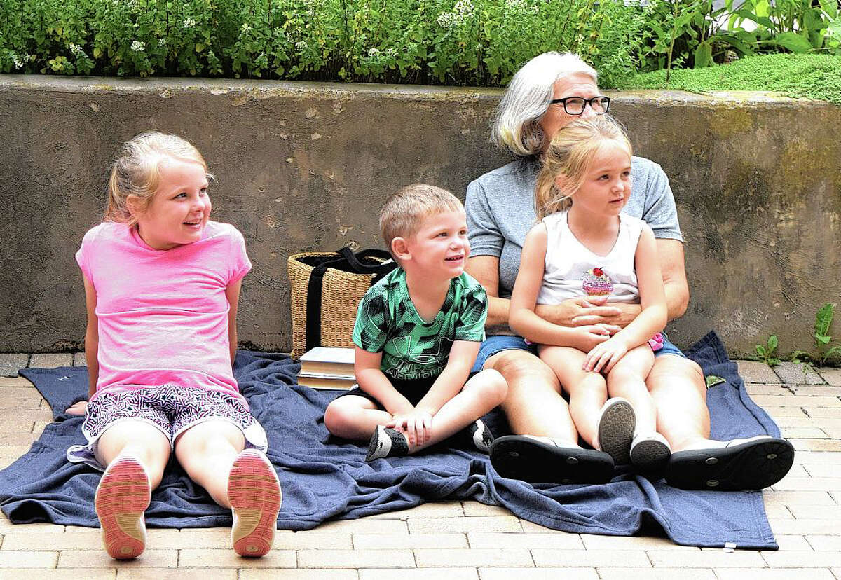 Children gather Tuesday at Jacksonville Public Library to watch professor Toto Johnson of Absolute Science perform science experiments as part of the Fire and Ice Show.
