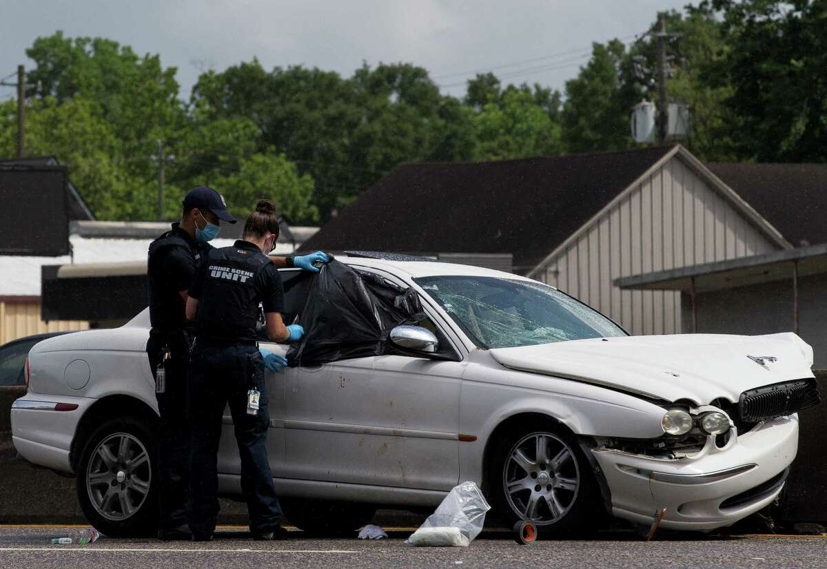 Houston Police officers cover broken windows with plastic bags as it starts to rain at the scene of a fatal road rage shooting that took place on the northbound lanes of Interstate 45 near Griggs Road on Monday, May 17, 2021, in Houston.