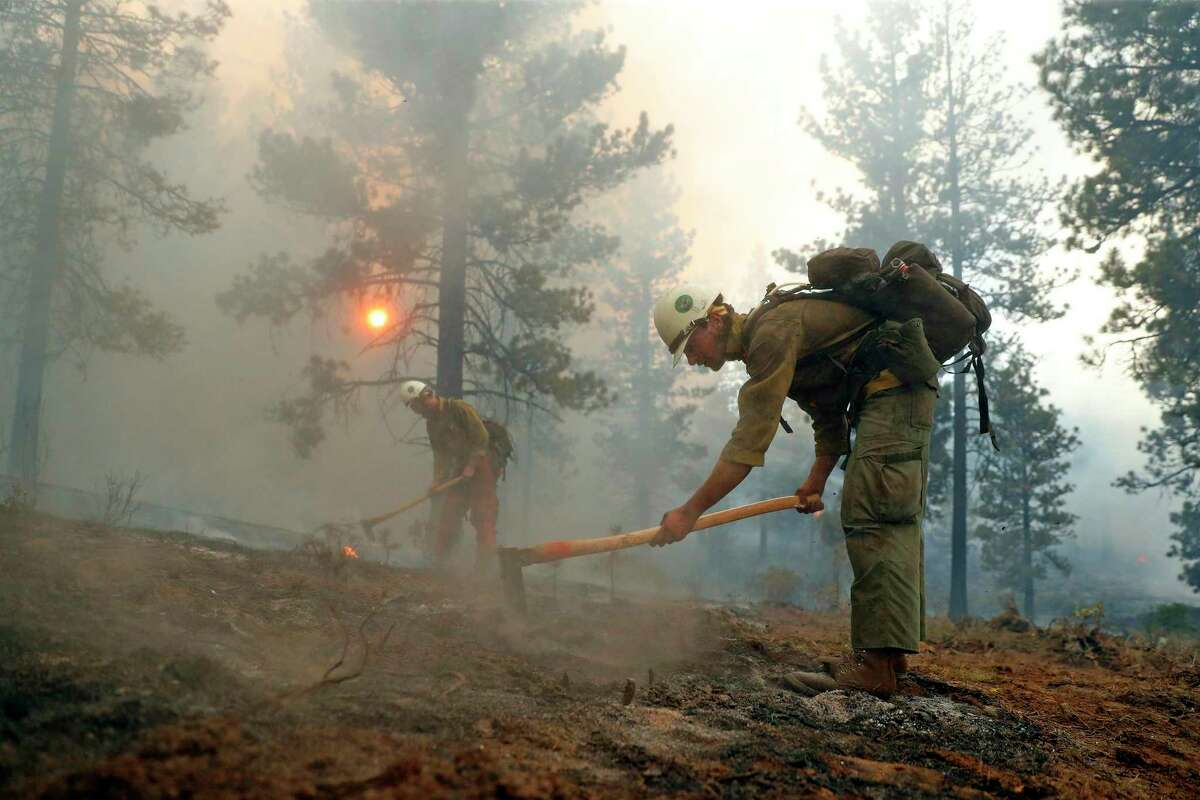 Fire crew members Gabriel Scarlett (left) and Julian Minuzzo work to put out hot spots in the Beckwourth Complex fireon Monday.