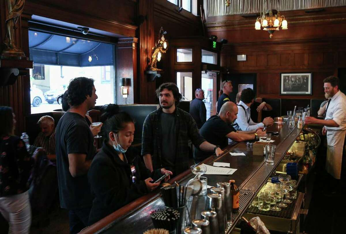 Jacob Hunt, center, waits to order a drink from the bar while with colleagues at House of Shields in San Francisco, Calif. on Thursday, June 24, 2021.