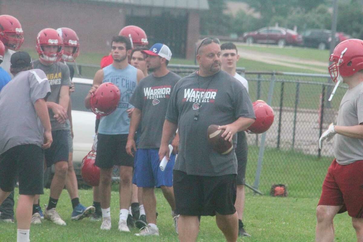 Chippewa Hills football coach Mark PeLong (right) works with his team on Monday during a 7-on-7 passing scrimmage.(Pioneer photo/John Raffel)