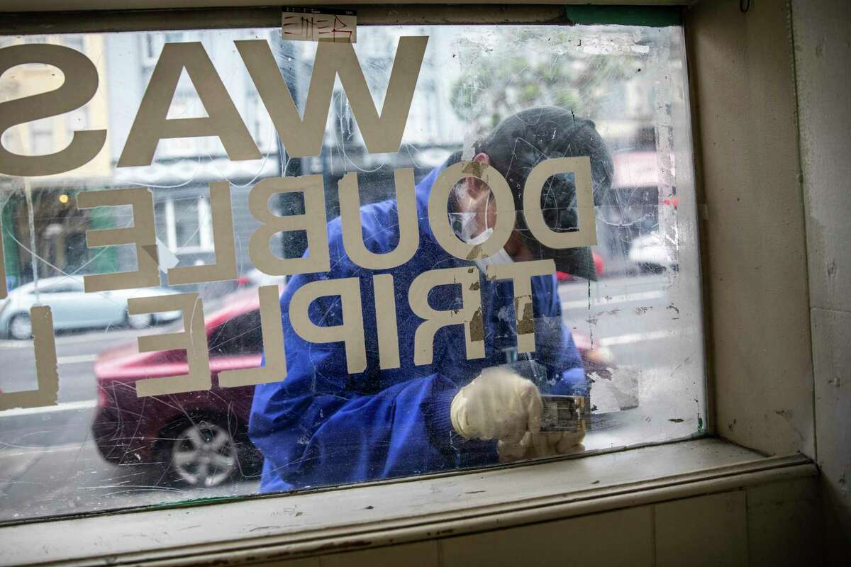 LeBron Gonzalez, a clean team member with the Tenderloin Community Benefit District, removes a sticker from a storefront window in San Francisco.