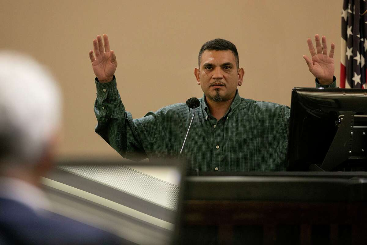 Witness Ricky Lee Martinez, who was pulled over by San Antonio Police Detective Benjamin Marconi moments before Marconi was shot, demonstrates Tuesday how he put his hands in the air as he approached the patrol car to check on Marconi's condition after watching him get shot.