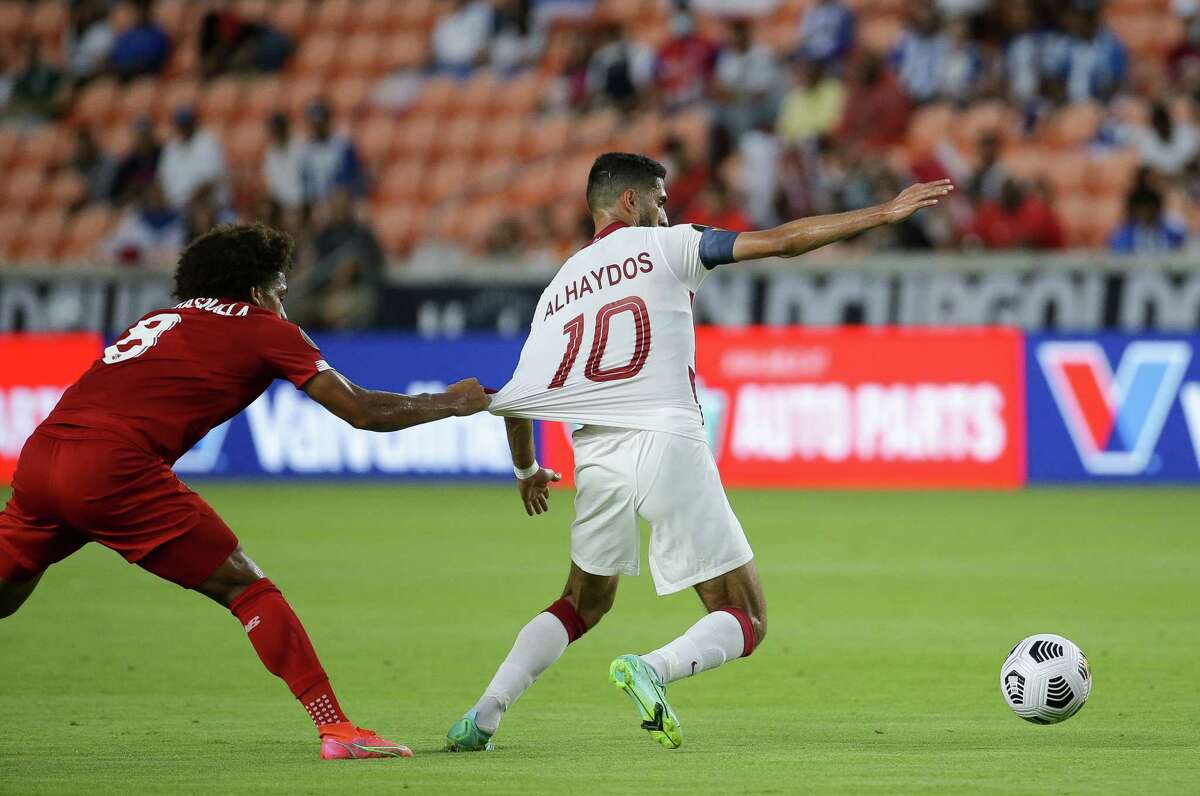 Panama midfielder Adalberto Carrasquilla (8) pulls on the jerseys of Qatar forward Hassan Al-Haydos (10) during the first half of a CONCACAF Gold Cup group stage match at BBVA Stadium on Tuesday, July 13, 2021, in Houston.