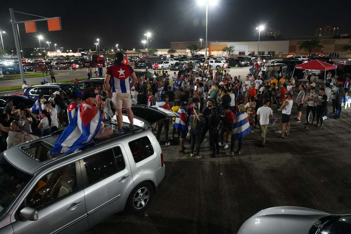 A group of demonstrators waving Cuban flags gathers in the parking lot of PlazAmericas on Bellaire Boulevard on Tuesday, July 13, 2021.