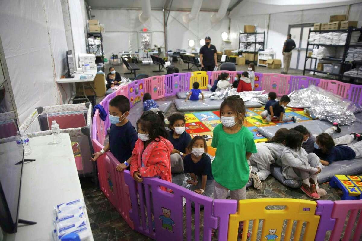 In this March 30, 2021 file photograph, young unaccompanied migrants, from ages 3 to 9, watch television inside a playpen at the U.S. Customs and Border Protection facility, the main detention center for unaccompanied children in the Rio Grande Valley, in Donna, Texas.