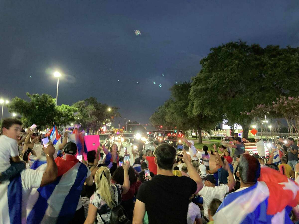 Demonstrators sit down in the middle of a Bellaire intersection near US 59 to block traffic in support of similar street protests in Cuba on Tuesday, July 13, 2021.