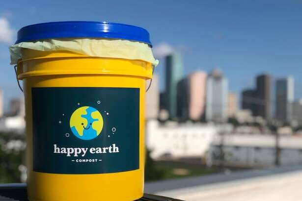 Happy Earth Compost's outdoor compost bucket against Houston's skyline.
