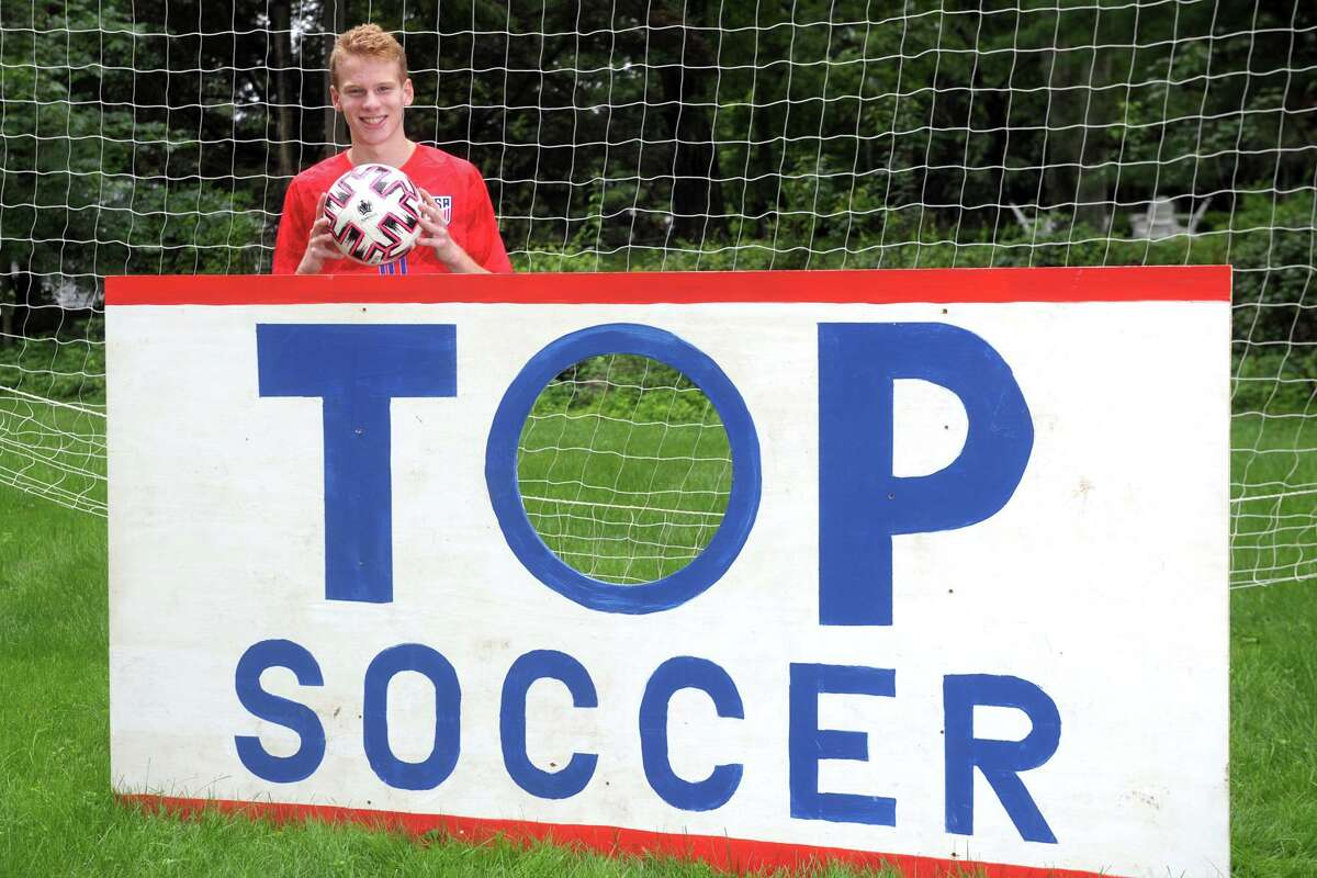 """Staples High School soccer player Bruno Guiduli poses behind the goal he designed and built for the """"goal-a-thon"""" fundraiser he has organized, in Westport, Conn. July 13, 2021."""