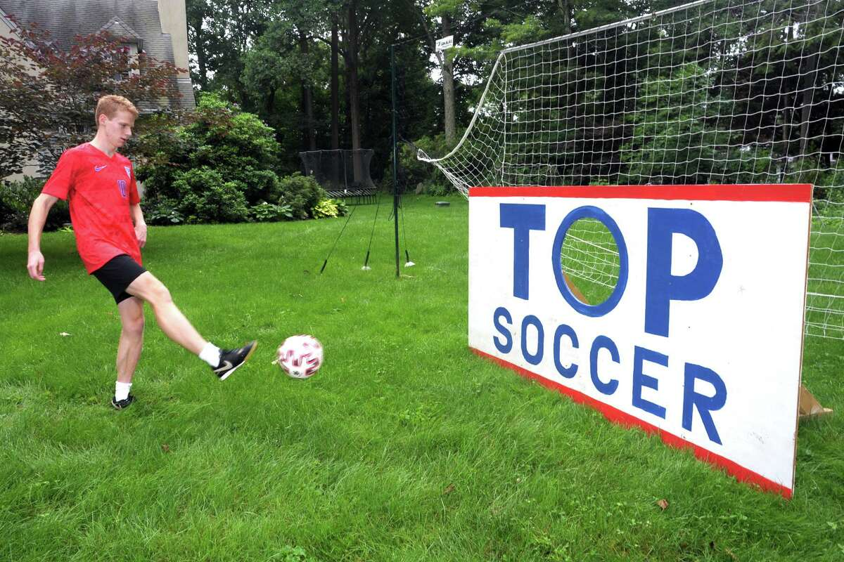 """Staples High School soccer player Bruno Guiduli kicks a ball towards the goal he designed and built for the """"goal-a-thon"""" fundraiser he has organized, in Westport, Conn. July 13, 2021."""