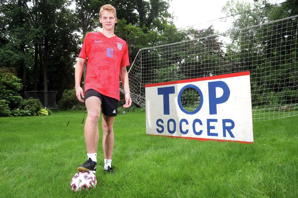 """Staples High School soccer player Bruno Guiduli poses in front of the goal he designed and built for the """"goal-a-thon"""" fundraiser he has organized, in Westport, Conn. July 13, 2021."""