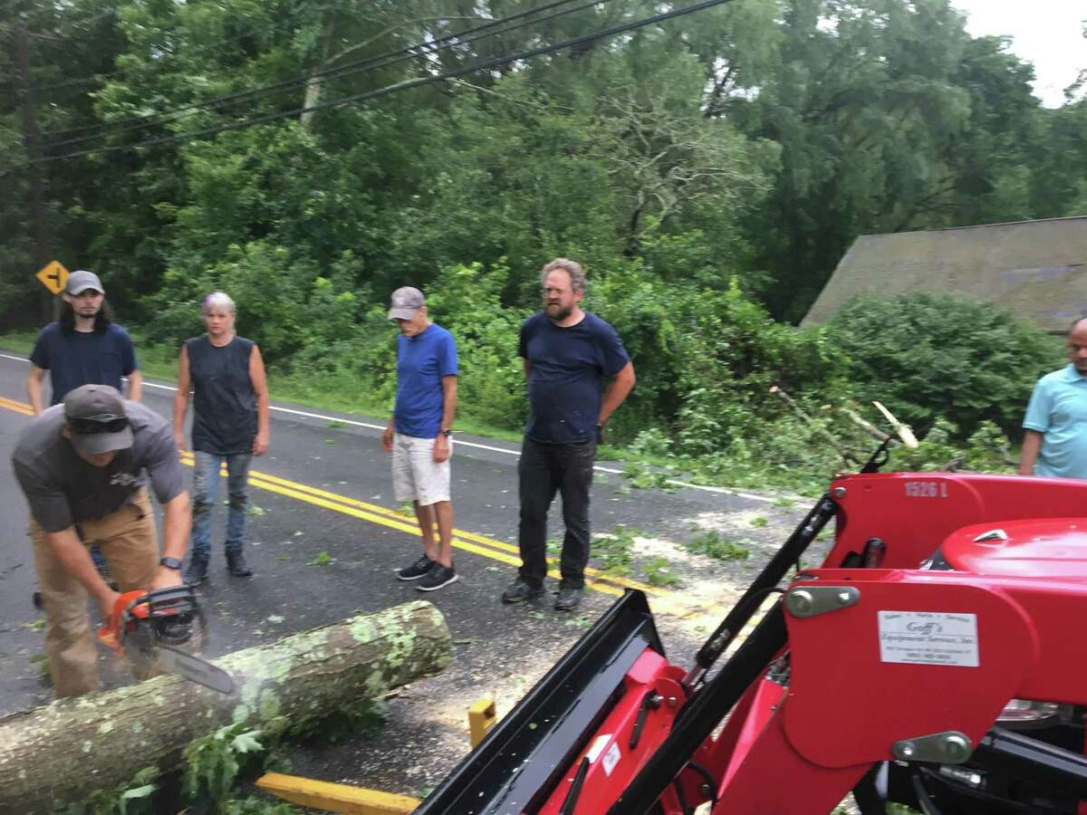 Local residents all pitch in to get a tree off the road in Kent